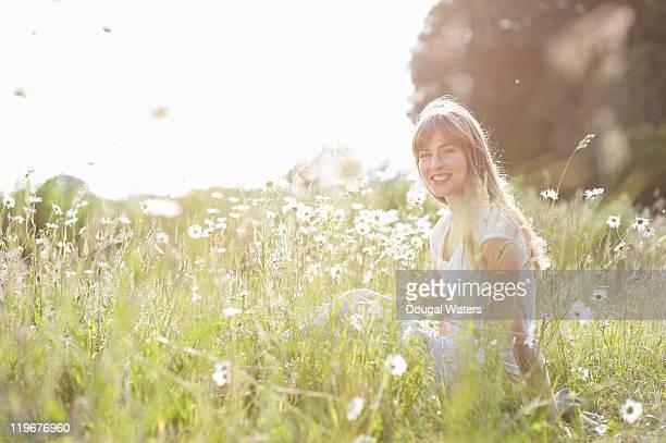 Woman sitting in wild flower meadow.