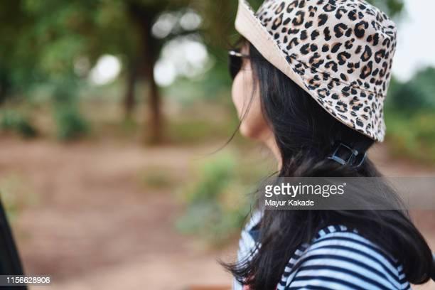 woman sitting in wildlife safari vehicle - レオパード柄 ストックフォトと画像