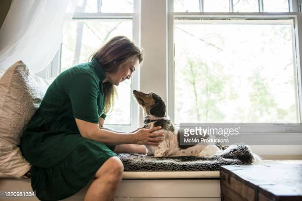 Woman sitting in window with dog