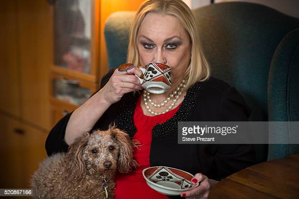 woman sitting in wing chair drink coffee with her dog on her lap looking at the camera - coffee drink stock pictures, royalty-free photos & images