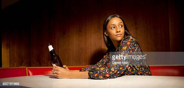 Woman sitting in wood panelled booth holding beer bottle looking away