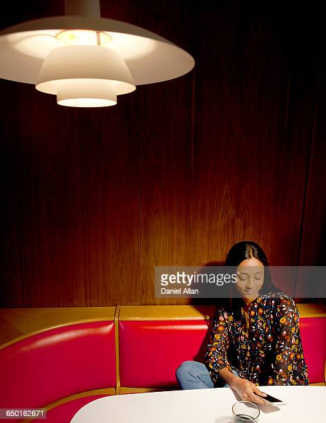 Woman sitting in wood panelled booth looking down at smartphone