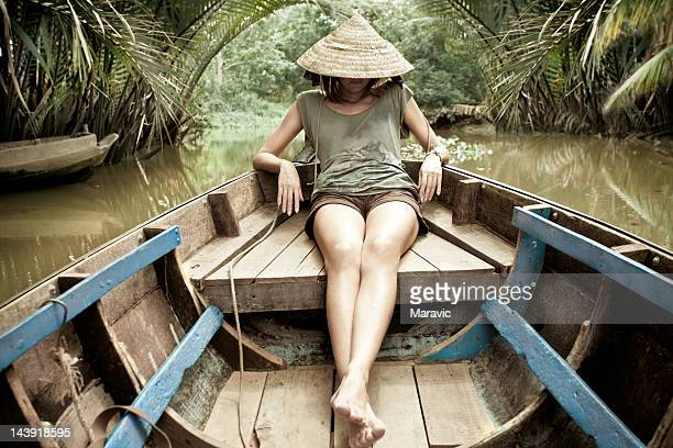 Woman sitting in wooden canoe in river of jungle