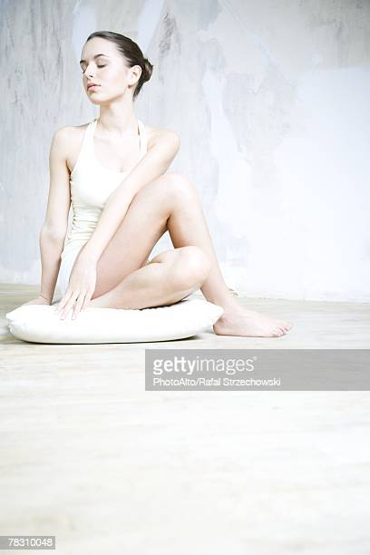 Woman sitting in yoga pose, full length