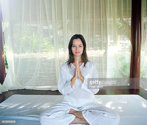 woman sitting in yoga position, bangkok, thailand - hugh sitton stock-fotos und bilder
