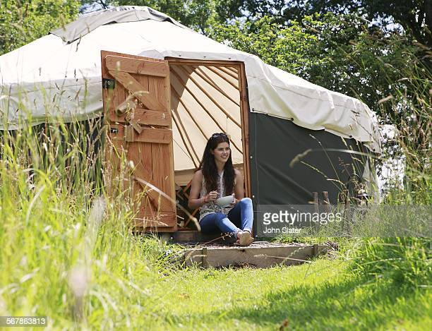 woman sitting in Yurt doorway eating cereal