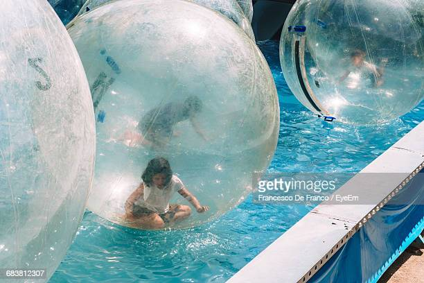 Woman Sitting In Zorb Ball Floating On Swimming Pool