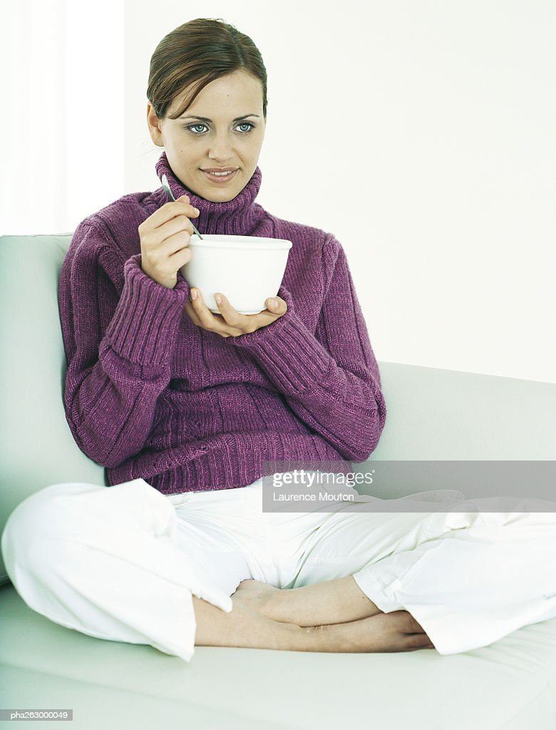 Woman sitting indian style on sofa holding bowl and utensil : Stockfoto