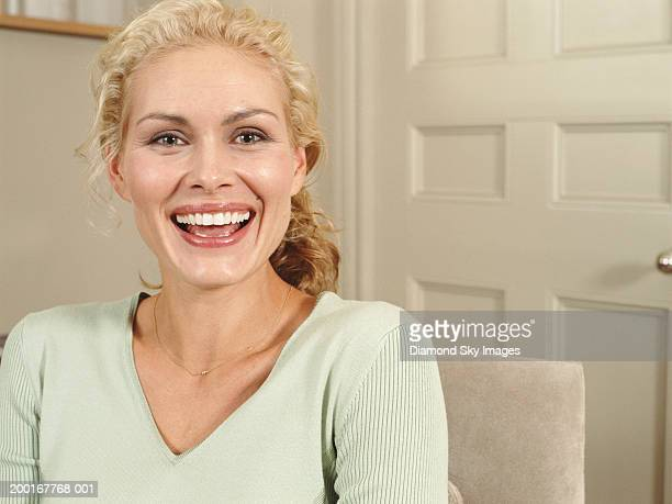 Woman sitting indoors, smiling, portrait