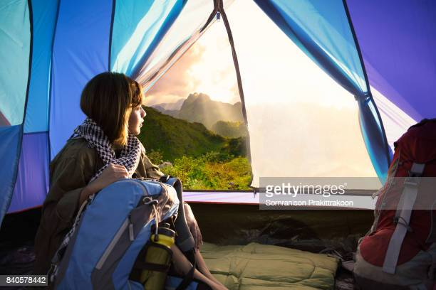 Woman sitting inside the blue camping tent