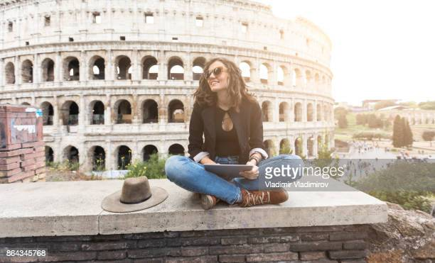 woman sitting legs crossed and resting - coliseum rome stock photos and pictures