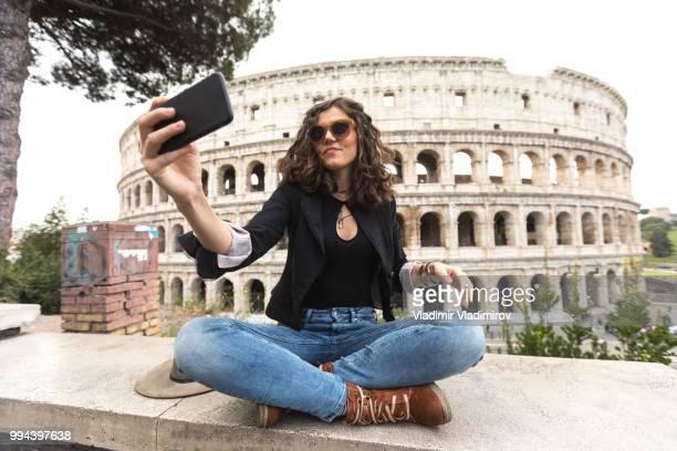 vrouw zitten benen gekruist en houdend selfie voor colosseum - antiek toestand stockfoto's en -beelden