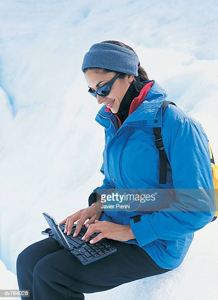 Woman Sitting near a Crevasse Using Her Laptop