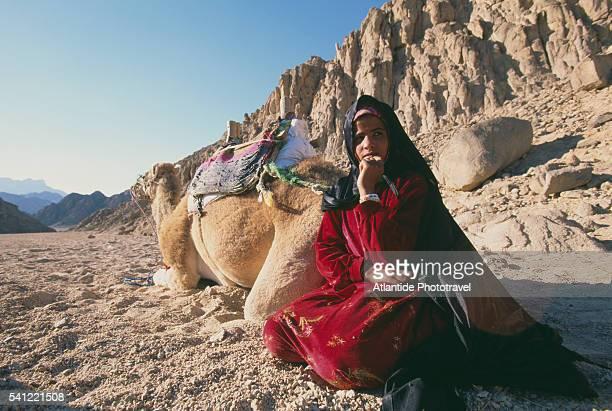 Woman Sitting Near Camel in Desert