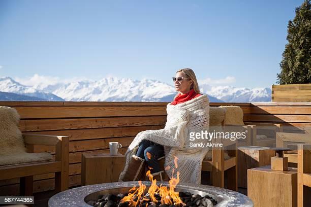Woman sitting near fire pit on the terrace of a hotel, Crans-Montana, Swiss Alps, Switzerland