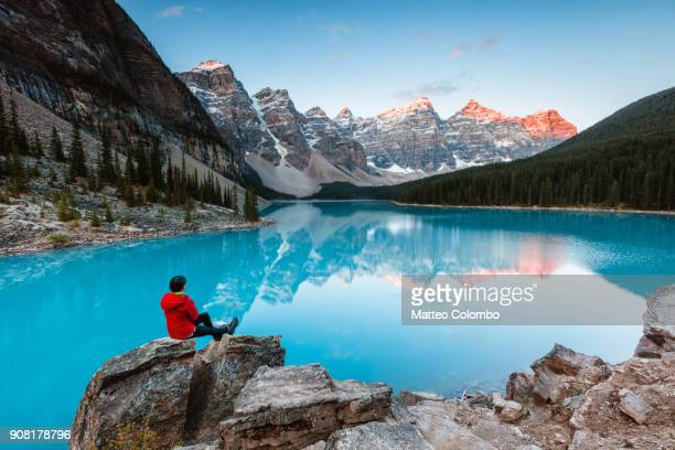 Woman sitting near Moraine lake, Banff, Canada