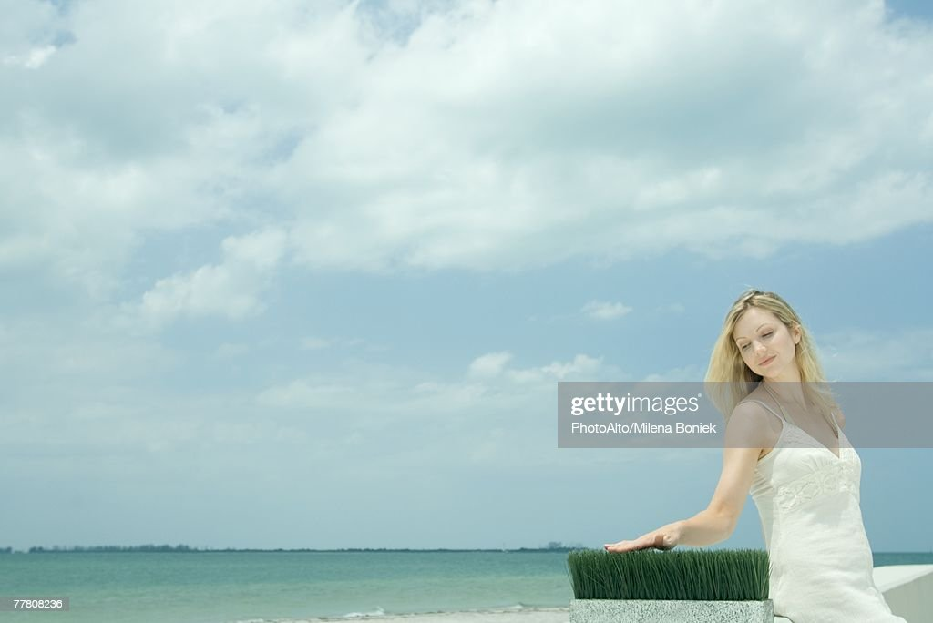 Woman sitting near sea, touching blades of wheat grass : Stock Photo