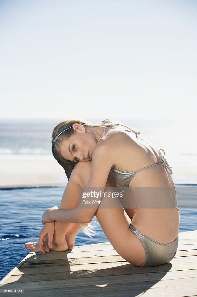 Woman sitting near swimming pool : Stock Photo