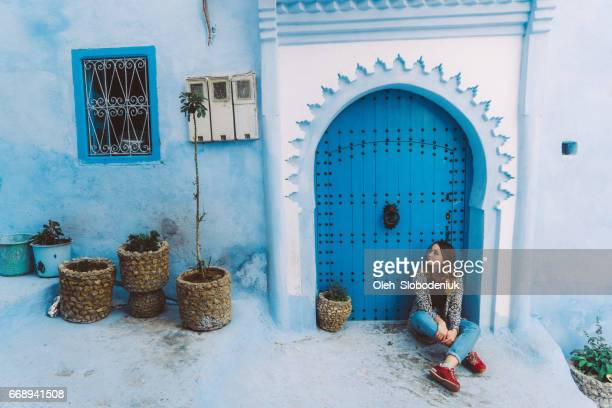 Woman sitting near the doors in Chefchaouen
