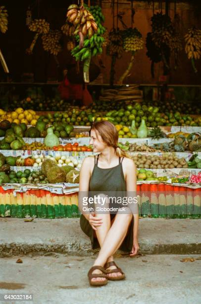 Woman sitting near the fruit shop in Sri Lanka