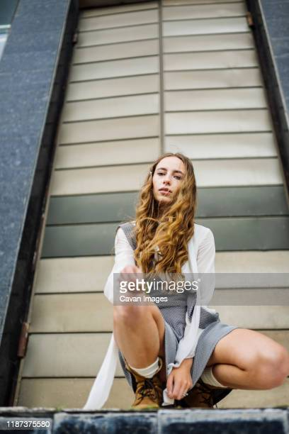 woman sitting near the gate - legs and short skirt sitting down stock pictures, royalty-free photos & images