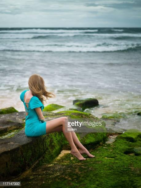 Woman sitting near the ocean