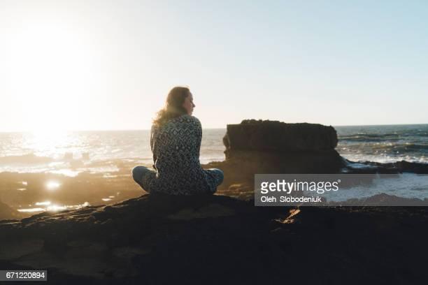 Femme assise près de la mer au Maroc