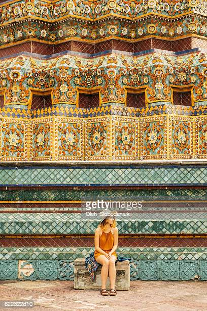 Woman sitting near the stupa in Wat Pho temple