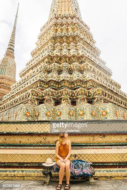 Woman sitting near the stupas in Wat Pho temple