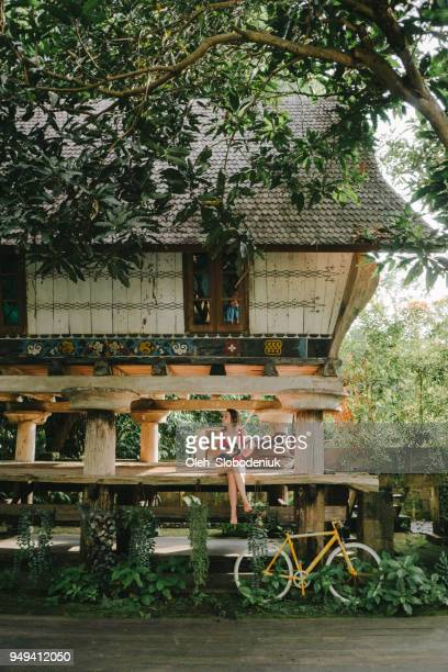 woman sitting near traditional sumatra house - balinese culture stock pictures, royalty-free photos & images