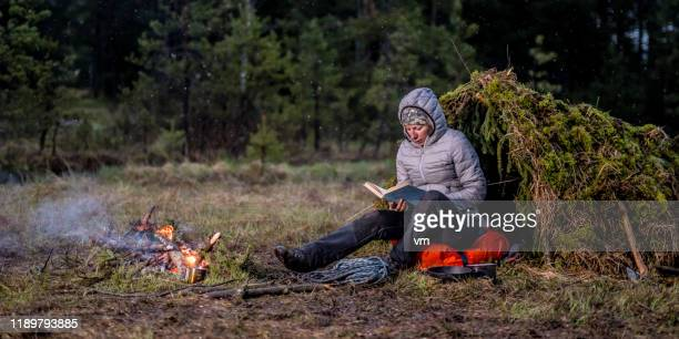 woman sitting next to a campfire and reading a book in nature - wilderness stock pictures, royalty-free photos & images