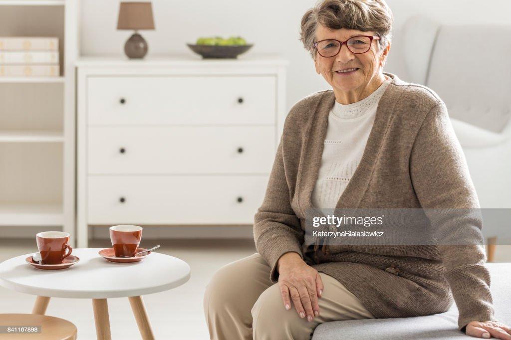 Woman sitting next to coffee table : Stock Photo
