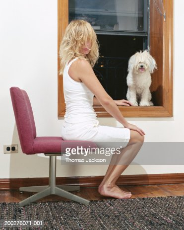 Woman Sitting Next To Dog On Window Sill Portrait High Res