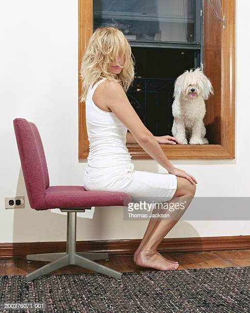 woman sitting next to dog on window sill, portrait - dog knotted in woman stock pictures, royalty-free photos & images