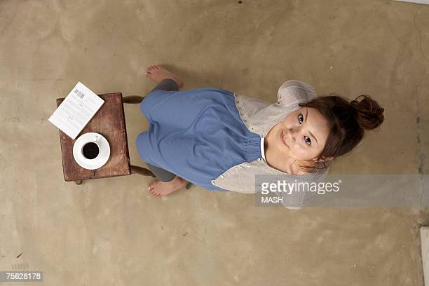 woman sitting next to small wooden table with coffee, overhead view, portrait - 若い女性一人 ストックフォトと画像