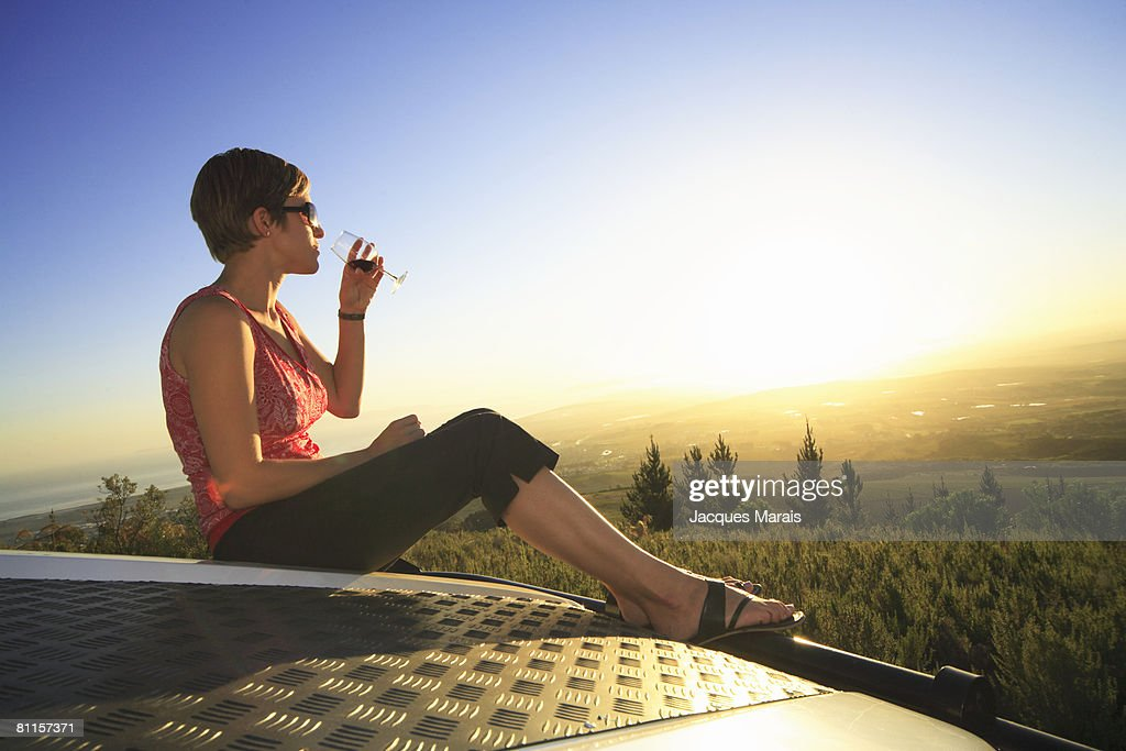 Woman sitting on a 4x4 vehicle tasting wine as sun sets in the Cape Winelands above Stellenbosch, Western Cape Province, South Africa : Stock Photo