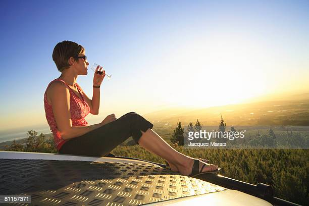 Woman sitting on a 4x4 vehicle tasting wine as sun sets in the Cape Winelands above Stellenbosch, Western Cape Province, South Africa