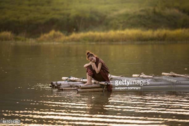 Woman sitting on a bamboo raft