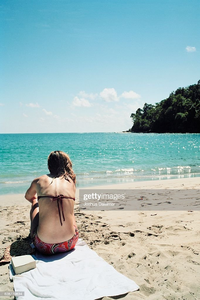 Woman sitting on a beach : Stock Photo