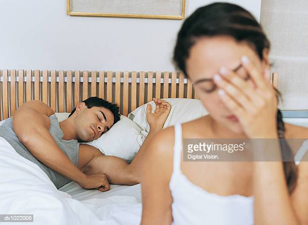 Woman Sitting on a Bed in a Bedroom, Man Sleeping