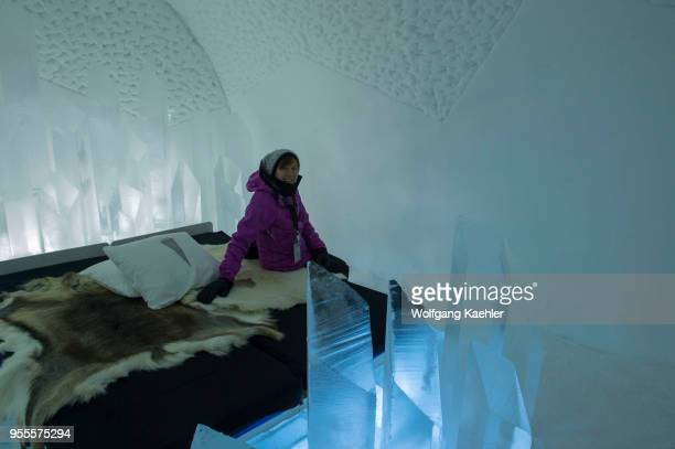 A woman sitting on a bed in a Cold Room in the classic Icehotel in Jukkasjarvi near Kiruna in Swedish Lapland northern Sweden