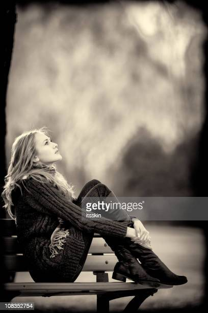 Woman sitting on a bench. Autumn style.