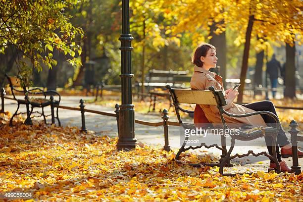 Frau sitzt auf einer Bank im park von Krakau.