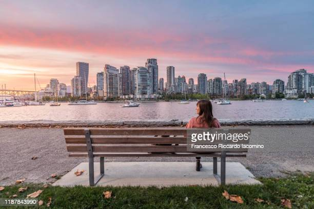 woman sitting on a bench looking at vancouver skyline, sunset from from the island park walk. british columbia, canada - vancouver canada stock pictures, royalty-free photos & images