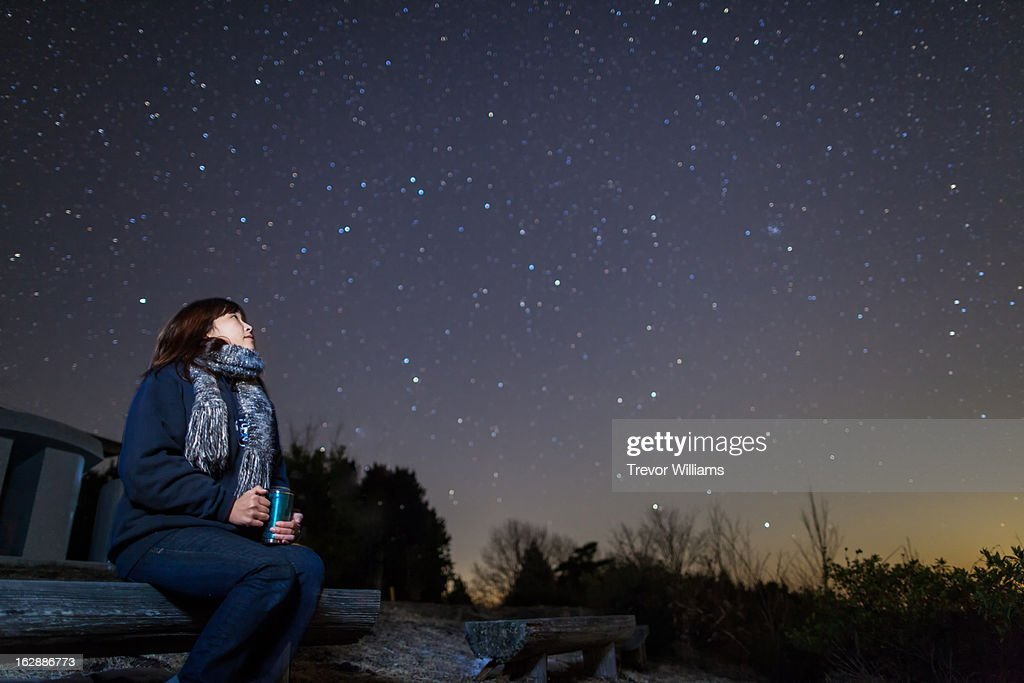 A woman sitting on a bench looking up at stars : Stock Photo