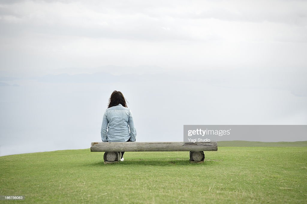 Woman sitting on a bench : Stock Photo