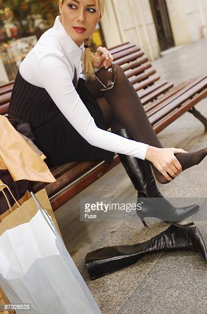 woman sitting on a bench, rubbing her feet - nylon feet stock photos and pictures