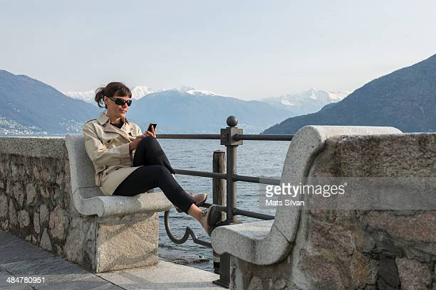 Woman sitting on a bench with her smartphone