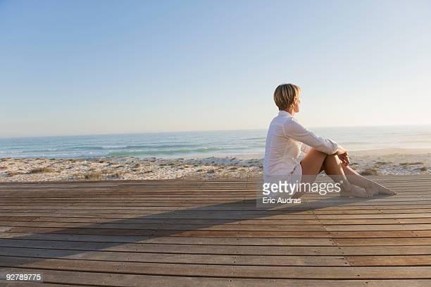 Woman sitting on a boardwalk