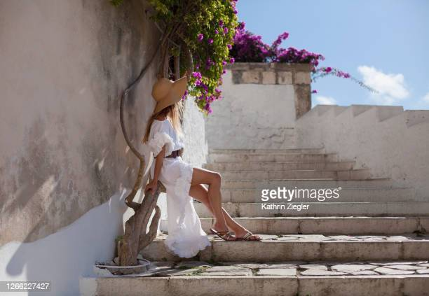 woman sitting on a bougainvillea trunk, wearing a beautiful white dress - long dress stock pictures, royalty-free photos & images